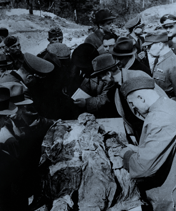 A group of people leaning over a body during the exhumation
