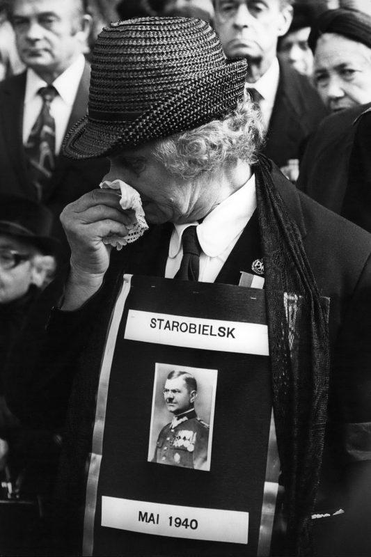 В. Пиотровска во время церемонии открытия памятника стоит с фотографией ее мужа, капитана Ксаверы Пиотровского с надписью «Старобельск, май 1940»